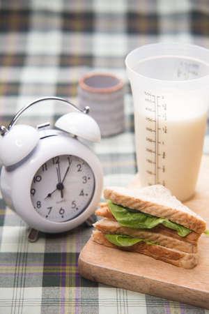 sandwich and glass of fresh milk on cutting board