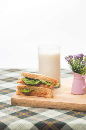 toasted: sandwich and glass of fresh milk on cutting board