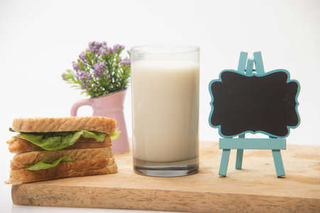 Sandwich and glass of fresh milk, blackboard 免版税图像