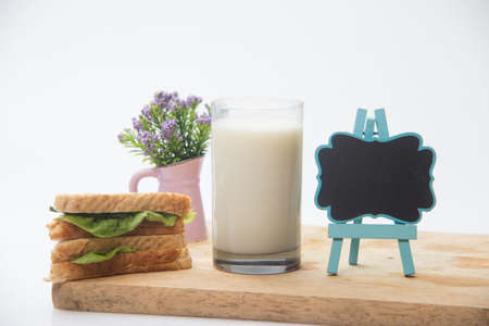 sandwich, a glass of milk and blackboard on cutting board, selective focus 免版税图像