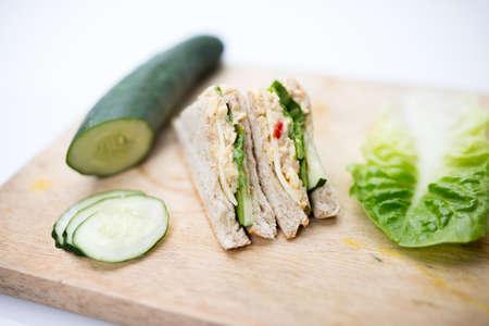 sandwich, cucumber and salad on cutting board 免版税图像