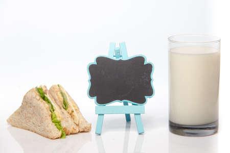 sandwich and glass of fresh milk, blackboard in middle 免版税图像