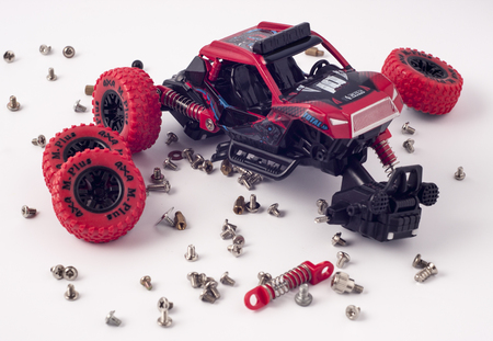 Disassembled car and scattered parts. Broken toy isolated on white background