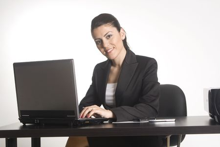 webdesigner: Businesswoman working on a computer at her office desk isolated against a white background.