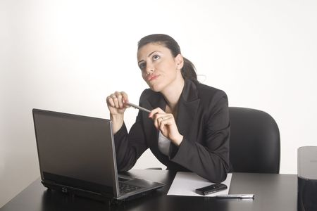Businesswoman working on a computer at her office desk isolated against a white background. Stock Photo - 5266976