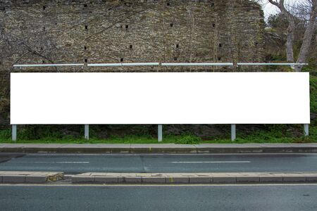 Blank billboard at the roadside photographed from the opposite sidewalk, with an old castle in the background