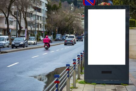 Big blank billboard on the sidewalk on a crowded road with cars driving in the city