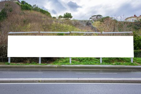 Blank billboard at the roadside photographed from the opposite sidewalk, with a deserted hill in the background