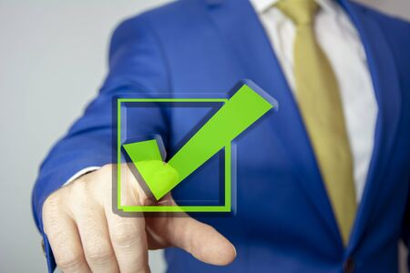 business man touching check mark on virtual screen with hand