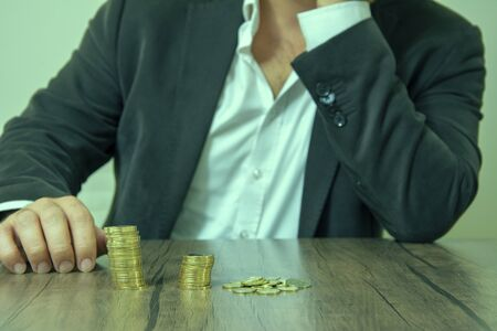 Stressed man looking at coins in front of him