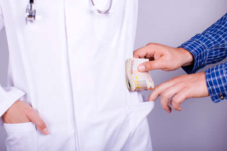 surgery expenses: Doctor corruption Stock Photo