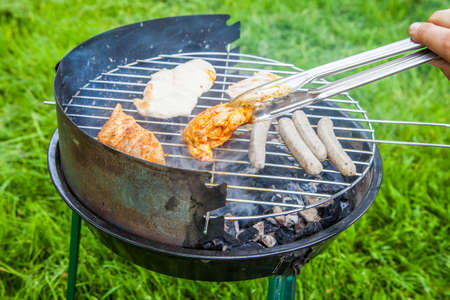 grill tongs sausage: BBQ Grill Stock Photo
