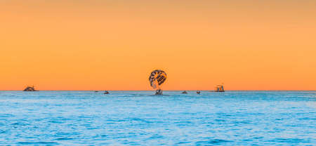 A boat with a parachute on the sky horizon with an orange sunset on the blue sea water background.