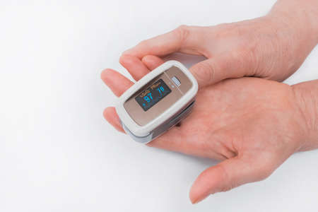 The hands of an elderly woman hold a modern device to measure the saturation of the pulse oximeter on a white background.