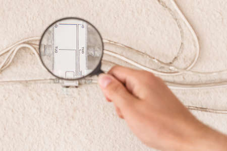 A worker's hand inspects a large antenna splitter with a magnifying glass, close-up.