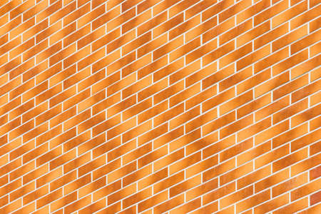 Diagonal, geometric modern light orange and brown brick wall building facade texture background.