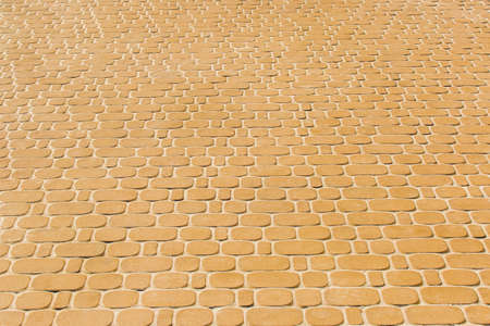 Light orange or yellow stone paving slabs floor tile urban texture background.