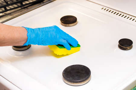 Woman's hand in a household glove sponges a gas stove. Cleaning the kitchen and washing the burners.