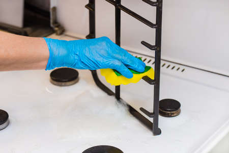 Hand of a woman in a household latex glove sponges the grate of a gas stove on kitchen, close up.