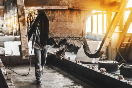 A construction worker controls the flow of concrete and gravel mix from a mixer in a rebar shop of an industrial plant, selective focus. Stock Photo