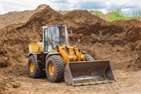 Belarus, Minsk - May 28, 2020: Bulldozer or tractor industrial heavy machine at a construction site against the background of a large pile of sand material.