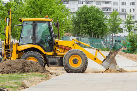 Bulldozer or excavator industrial machine removes sand on the background of buildings at a construction site.
