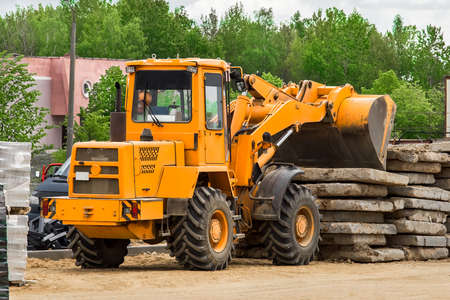 Bulldozer or excavator industrial heavy machine at a construction site unloads old concrete stone slabs material.