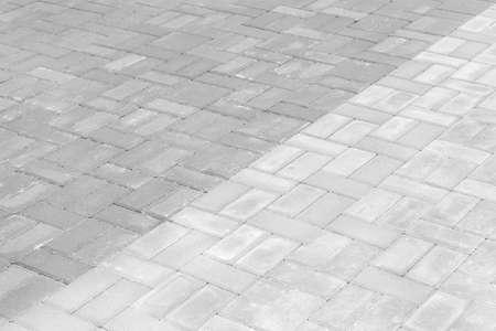 Gray paving slabs urban street road floor stone tile texture background. Stockfoto