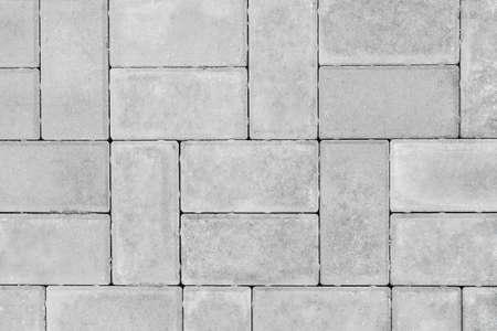 Gray paving slabs urban street road floor stone tile texture background, top view. Standard-Bild