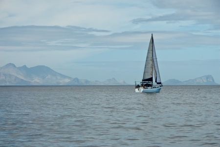 icey: The view of a sail boat on calm waters, with mountains in the back, Cape Town, South Africa Stock Photo