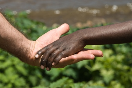 kids holding hands: The view of a childs hand being held by the hand of an adult, Rwanda Stock Photo