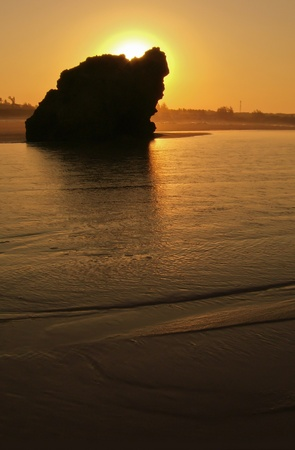 shallow water: The view of a rock in shallow water being lit by sun rays, South Africa Stock Photo