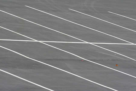 An empty parking lot at a marina with diagonal white stripes.