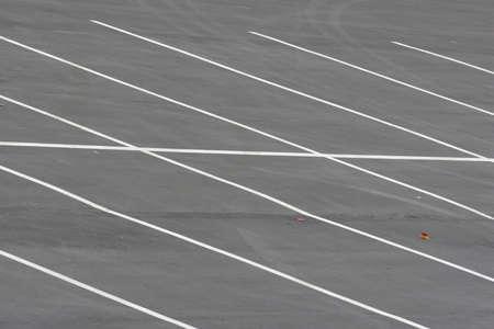 Een lege parkeerplaats in een jachthaven met diagonale witte strepen.