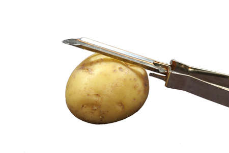 A small yellow potato ready for peeling with the peeler laying on top.