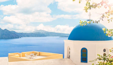view of orthodox church blue dome and open house terrace with flowers at foreground and mountains with sea at background on sunny summer day with sun shining in right upper corner, Oia, Santorini or Thira, Greece 版權商用圖片