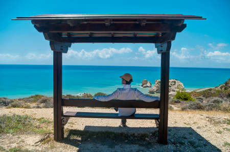 man sitting on bench looking at sea in Cyprus