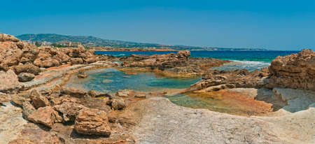 panoramic view of small sea pool at rocky coast with Mediterranean sea and mountains at background, Coral Bay, Cyprus