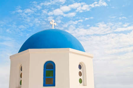 orthodox church with blue dome against blue sky on sunny summer day, Oia, Santorini or Thira, Greece