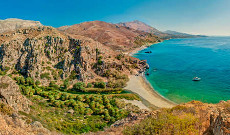 panoramic view of palm tree forest and beach of Preveli surrounded by mountains on sunny summer day, Crete, Greece