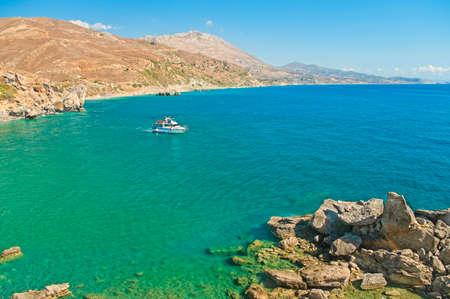 small white tourist boat at Preveli beach in crystal clear waters of Mediterranean sea in Crete, Greece