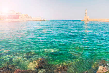 cross-processed shot of clear waters of Mediterranean sea in morning in old part of Chania with sun shining behind buildings, Crete