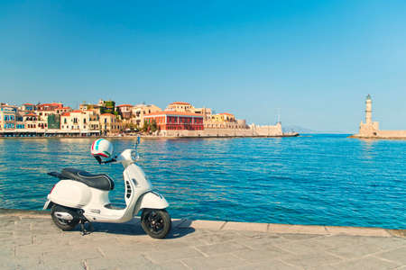 cross-processed image of white retro style scooter parked in harbour in Chania on sunny summer day with old city and venetian light-house at background, Crete Stock Photo