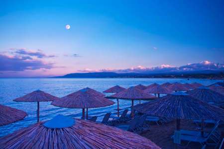 wooden umbrellas and sunbeds on beach at night with mountains and full moon at background in Georgioupolis, Crete, Greece
