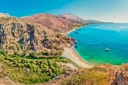 aerial view of palm tree forest and beach of Preveli surrounded by mountains on sunny summer day, Crete, Greece Stock Photo