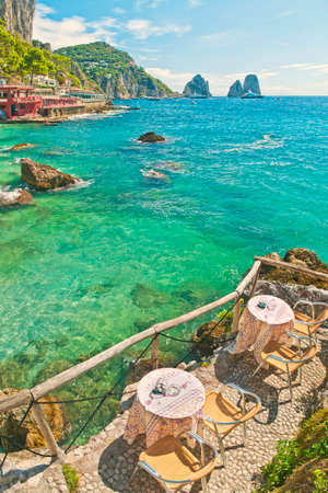 two tables on small terrace at cafe on marina piccola beach overlooking famous Faraglioni rocks on sunny summer day, Capri, Italy Stok Fotoğraf