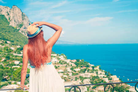 Cross-processed image of young red-haired girl wearing white dress and hat standing on balcony and looking at sea view, Capri, Italy