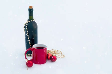 bottle of wine with red mug and christmas ornaments on snow with snow falling from sky