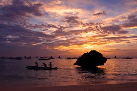 three men rowing a fishing boat at sunset near white beach, Boracay island, the Philippines