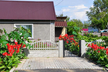 beautiful cozy landscaped private house with red flowers in summer photo